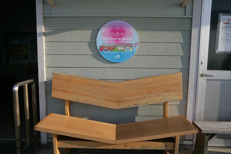 無人の駅舎にはらぶらぶベンチが置かれている。