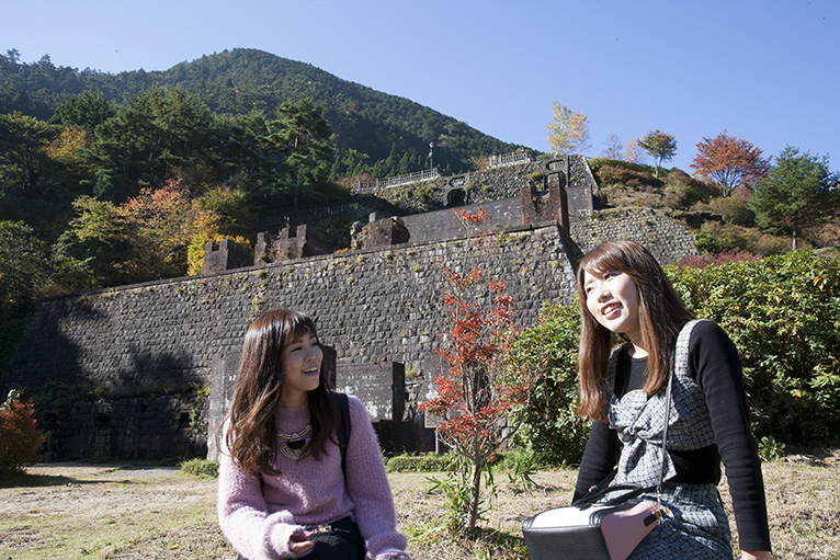 貯鉱庫跡を背景に観光客も記念写真。