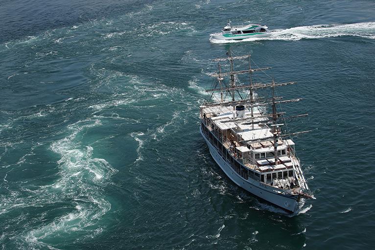 渦の道展望室から渦潮に突入する観潮船を見下ろす