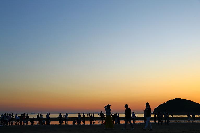 夕方が沈んでも、美しくフォトジェニックな海岸には多くの人がいっぱい