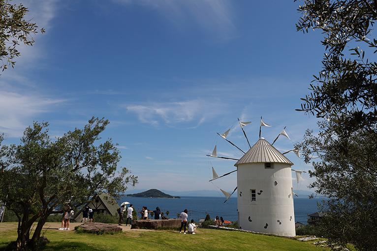 瀬戸内海の青い海とオリーブの木に囲まれたギリシャ風車