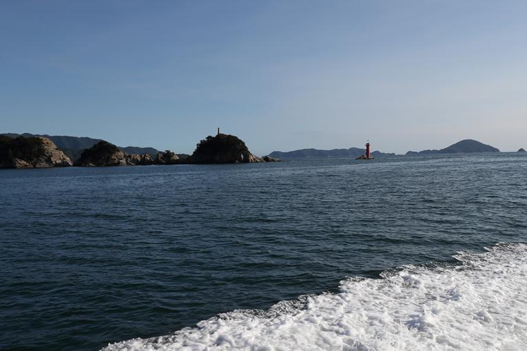 諏訪崎の白い魚霊塔と灯台が見える